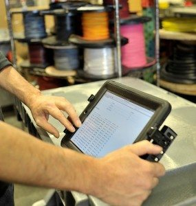 Employees use electronic tablets to access the real-time production database.
